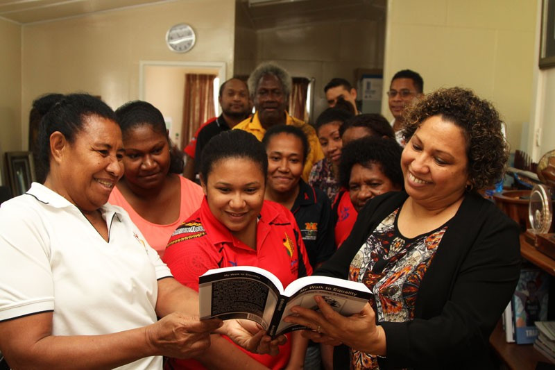 Alurigo Ravusiro, left, presented Auvita Rapilla, right, with the book ©PNGOC