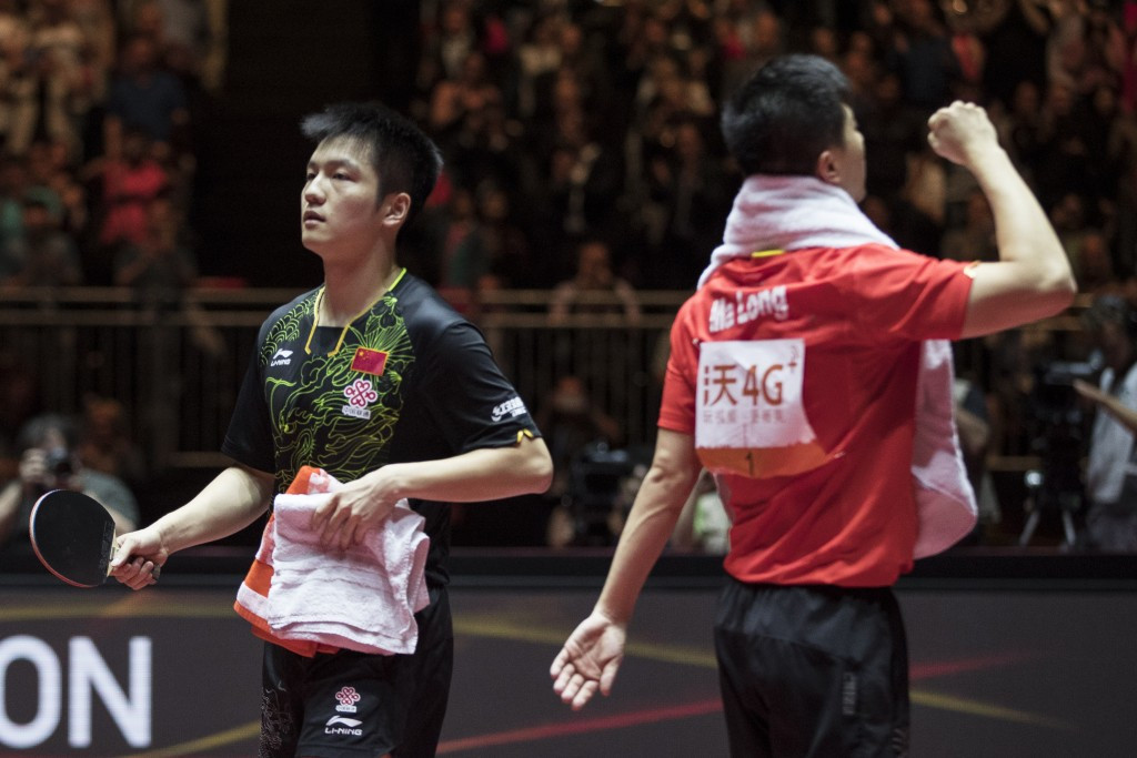 Ma Long, right, and Fan Zhendong cut contrasting figures at the end of the men's singles final ©Getty Images