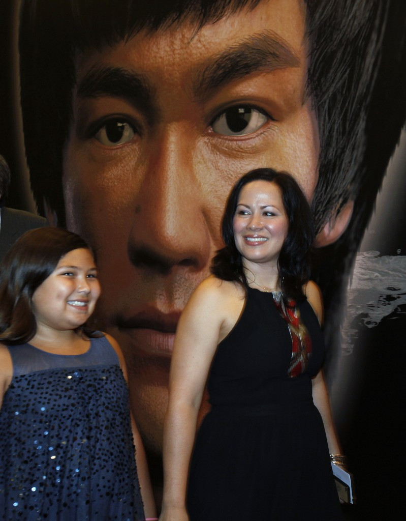 Bruce Lee's daughter, Shannon, walks with her daughter Wren past a poster in the Hong Kong Heritage Museum during the launch of a five-year display featuring the life of the late martial arts film star ©Getty Images