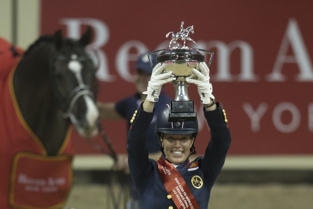 Charlotte Dujardin holds the new Reem Acra trophy aloft after making it a back-to-back double of victories with the amazing Valegro at the FEI World Cup Dressage 2015 Final ©FEI/Dirk Caremans