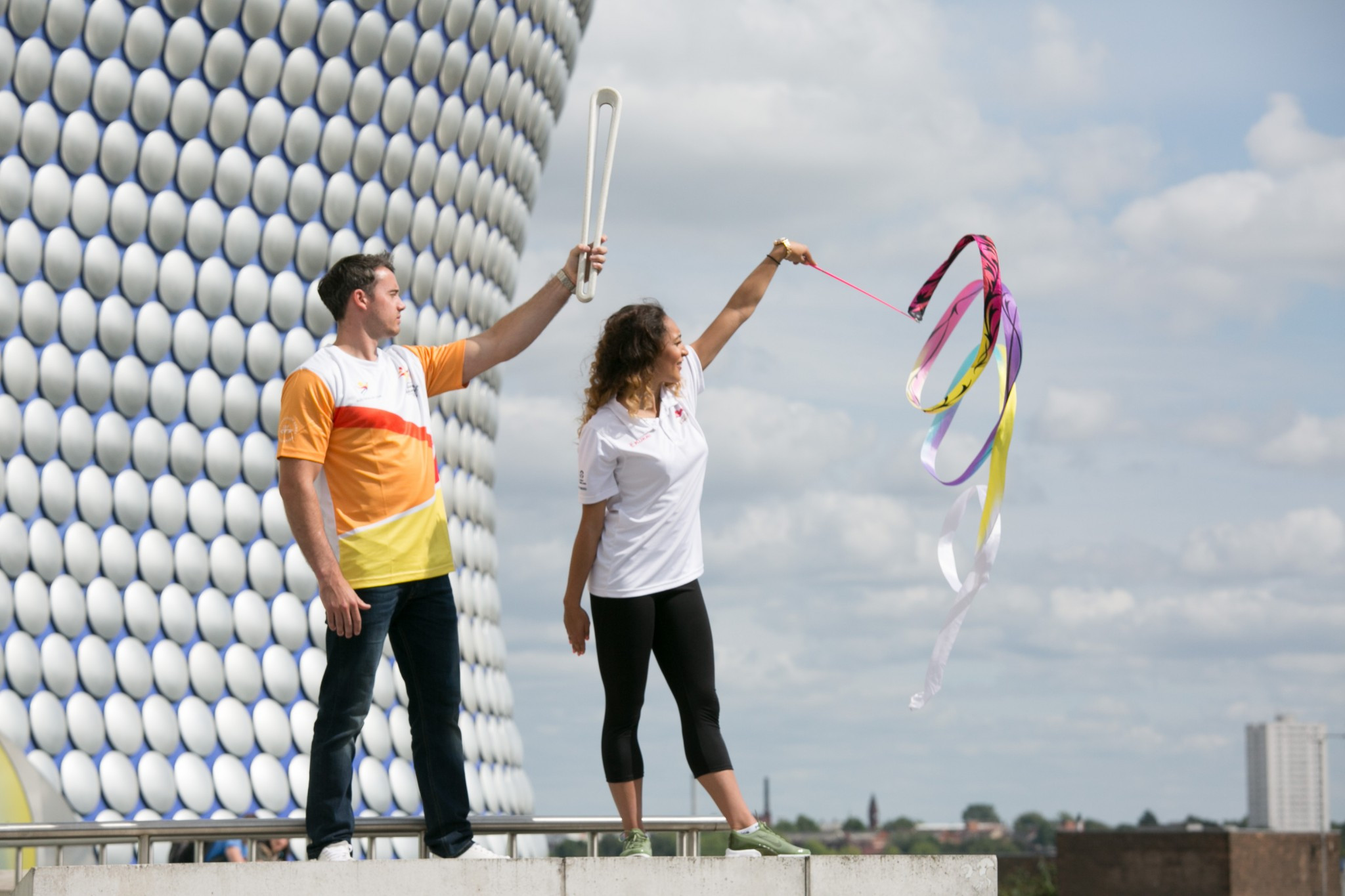 Gymnasts Kristian Thomas, a gold medallist at the Glasgow 2014 Commonwealth Games, and Mimi Cesar pose with the Baton outside the iconic Bullring in Birmingham ©Birmingham 2022