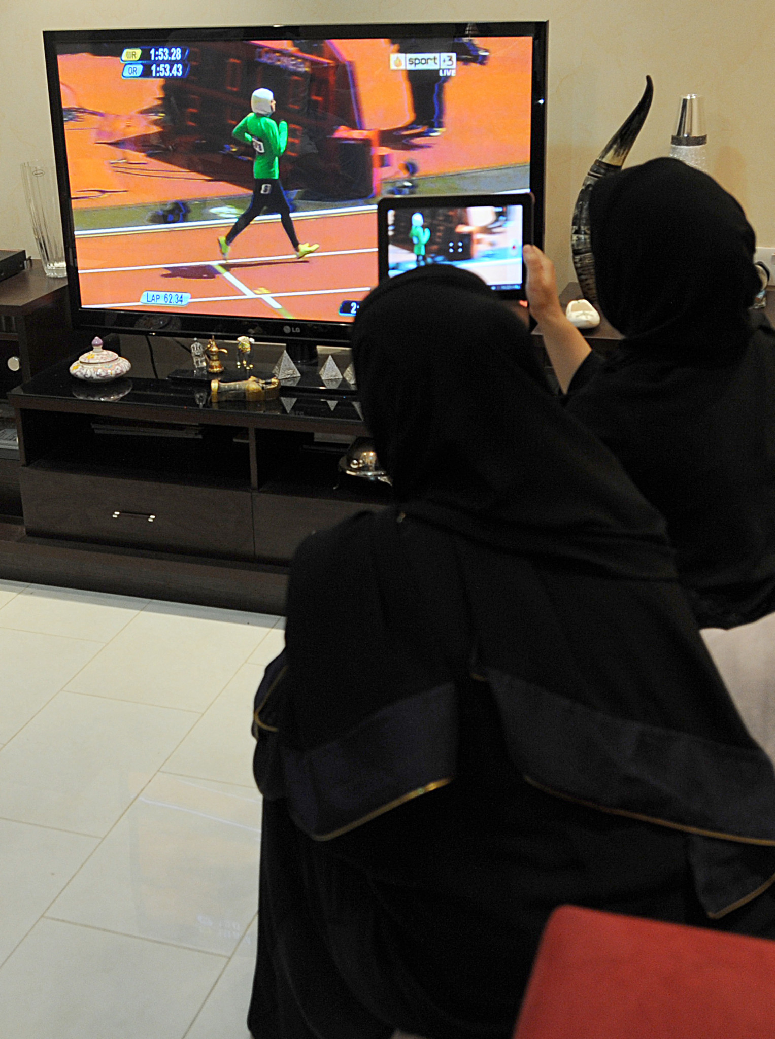Saudi women sit in a house in Riyadh watching and filming, via a tablet, Saudi Arabia's Sarah Attar competing in the women's 800m heats at the London 2012 Olympics ©Getty Images