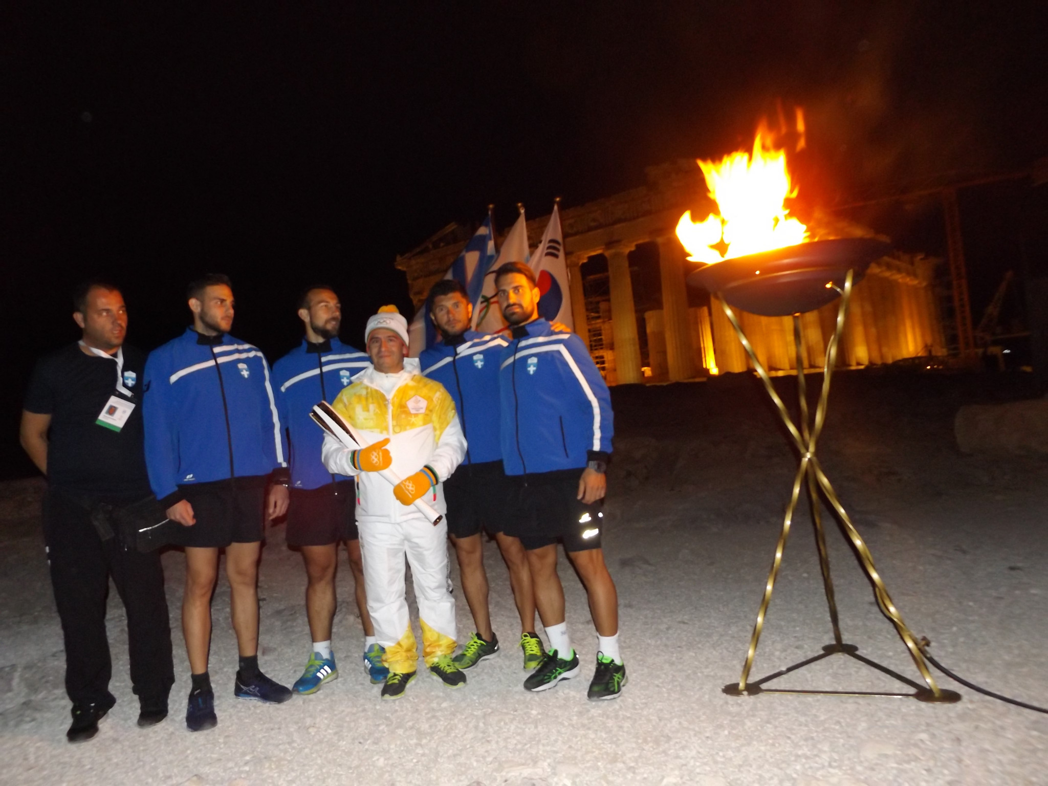 Athens 2004 gold medallist Dimosthenis Tampakos is pictured with Torch Relay organisers ©ITG