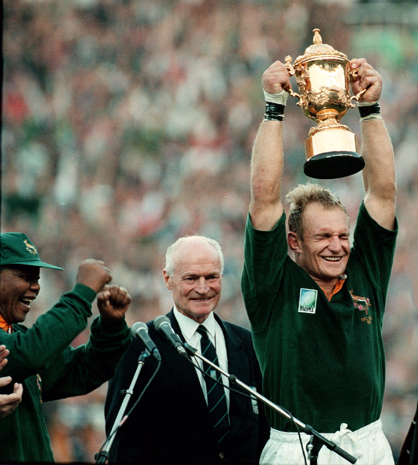 South Africa captain Francois Pienaar holds the 1995 World Cup aloft after defeating the New Zealand as President Nelson Mandela dances in joy ©Getty Images