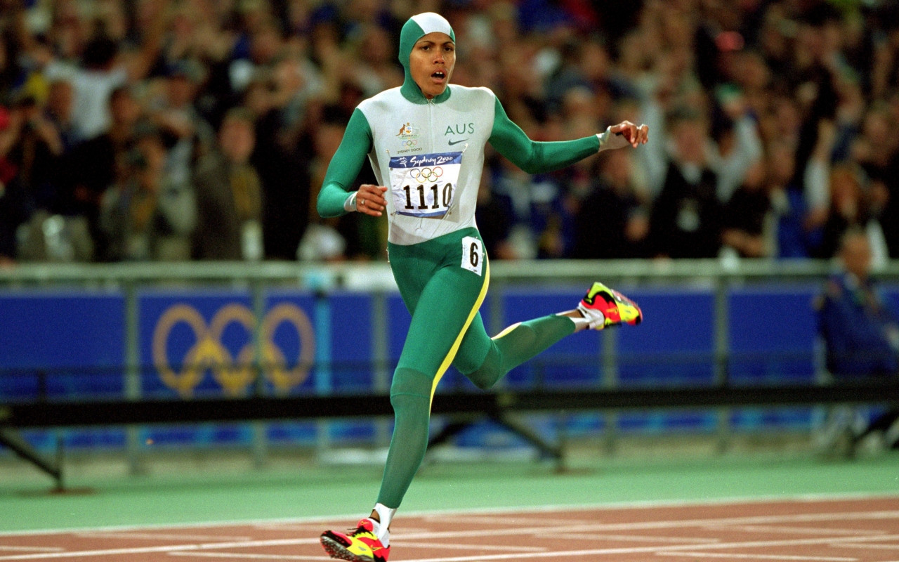 Cathy Freeman, carrying Australian colours on her running suit and Aboriginal colours on her shoes, thinking: