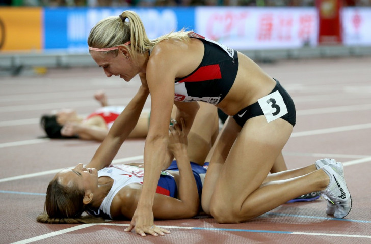 Britain's Olympic heptathlon champiion Jessica Ennis-Hill (grounded) is congratulated by silver medallist Brianne Theisen Eaton on regaining her world title ©Getty Images