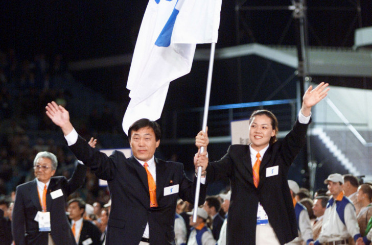 Pak Jang Choo, left, of North Korea, and Chung Eun-Soon of South Korea carry a special flag showing the Korean peninsula as teams from the two Koreas march together for the first time at the Opening Ceremony of the 2000 Sydney Games ©Getty Images