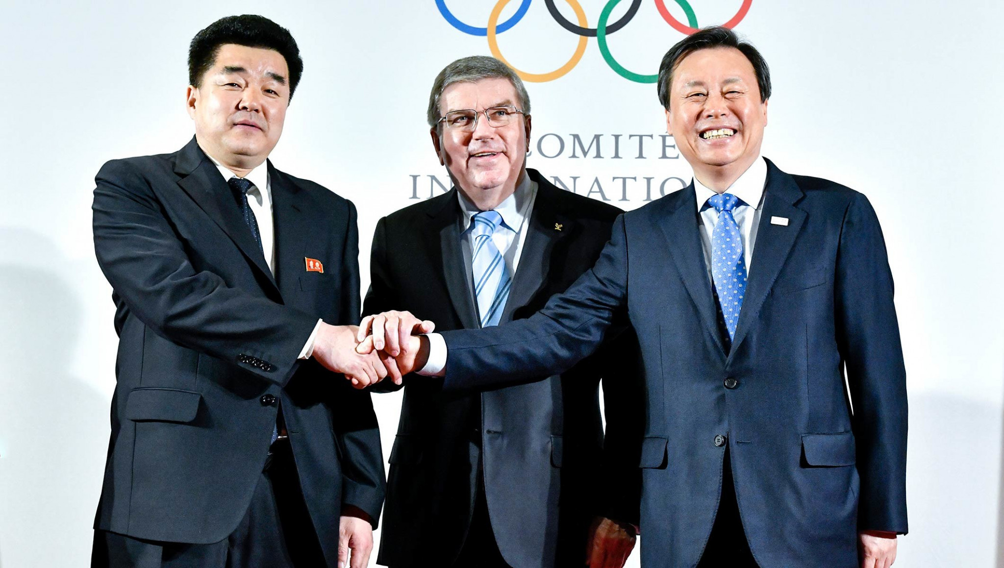 IOC President Thomas Bach, centre, alongside representatives from North and South Korea ©IOC