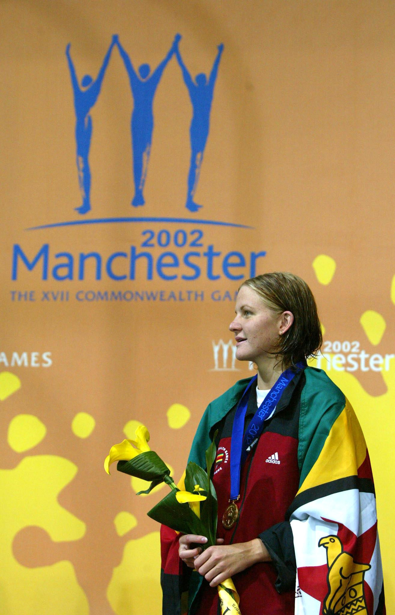 Zimbabwe's Kirsty Coventry celebrates winning a 200m individual medley gold medal at the Manchester 2002 Commonwealth Games - the last time her country competed in the event ©Getty Images