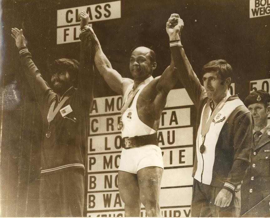 Precious McKenzie celebrates winning his third consecutive Commonwealth Games gold medal at Christchurch 1974, a performance watched by the Queen and Duke of Edinburgh ©Getty Images