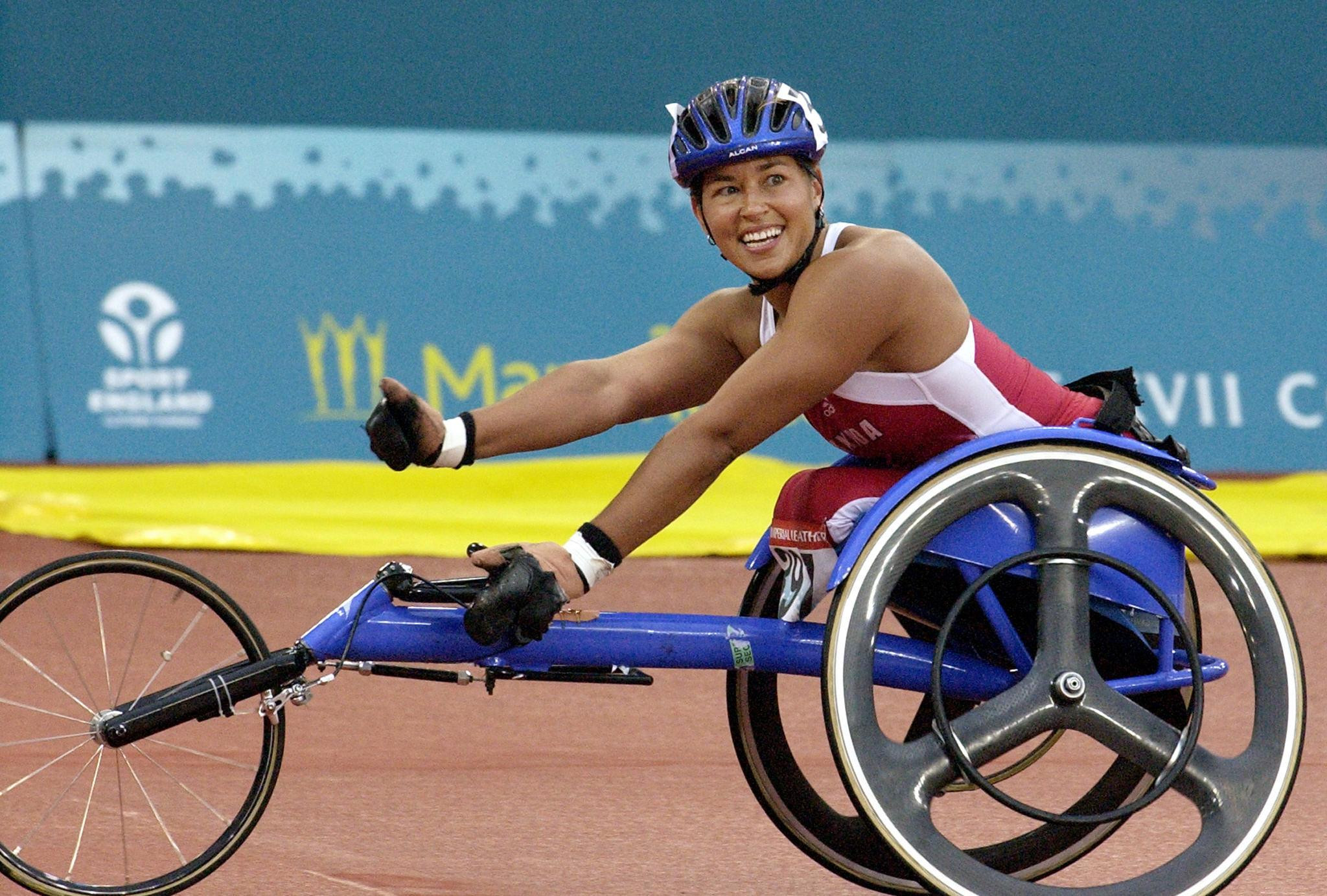 Chantal Petitclerc celebrates after making history by becoming the first athlete to win a gold medal in a Para-sport event at Manchester 2002 ©Getty Images