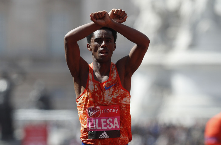 Ethiopia's Feyisa Lilesa, pictured making his familiar gesture of solidarity with his beleaguered Oromo people after running last year's London Marathon, will seek to regain the Tokyo title he won in 2016 ©Getty Images