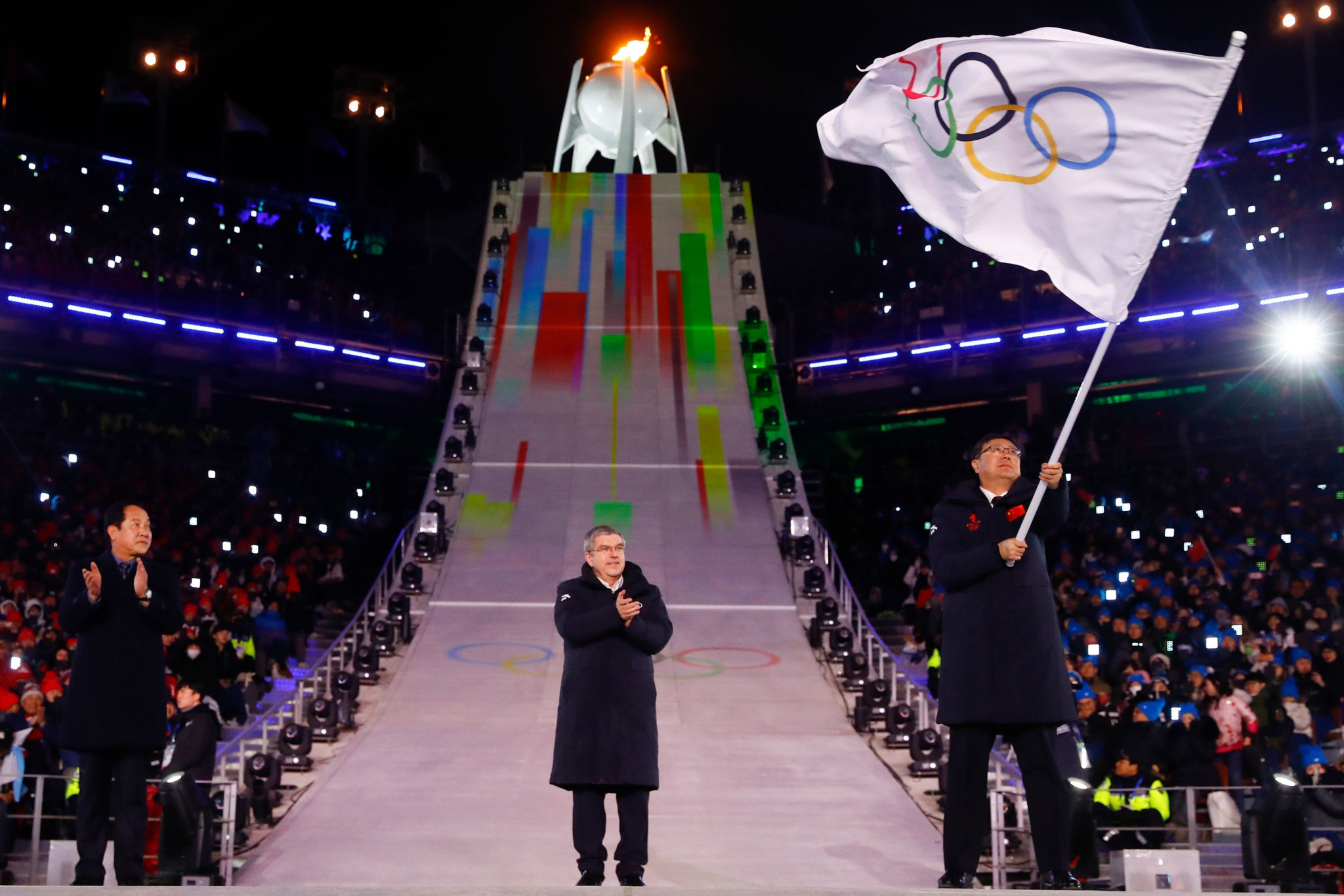 Beijing Mayor Chen Jining waves the Olympic flag during the Pyeongchang 2018 Closing Ceremony to mark the fact the Chinese city will host the 2022 Olympics as IOC President Thomas Bach watches on ©Getty Images