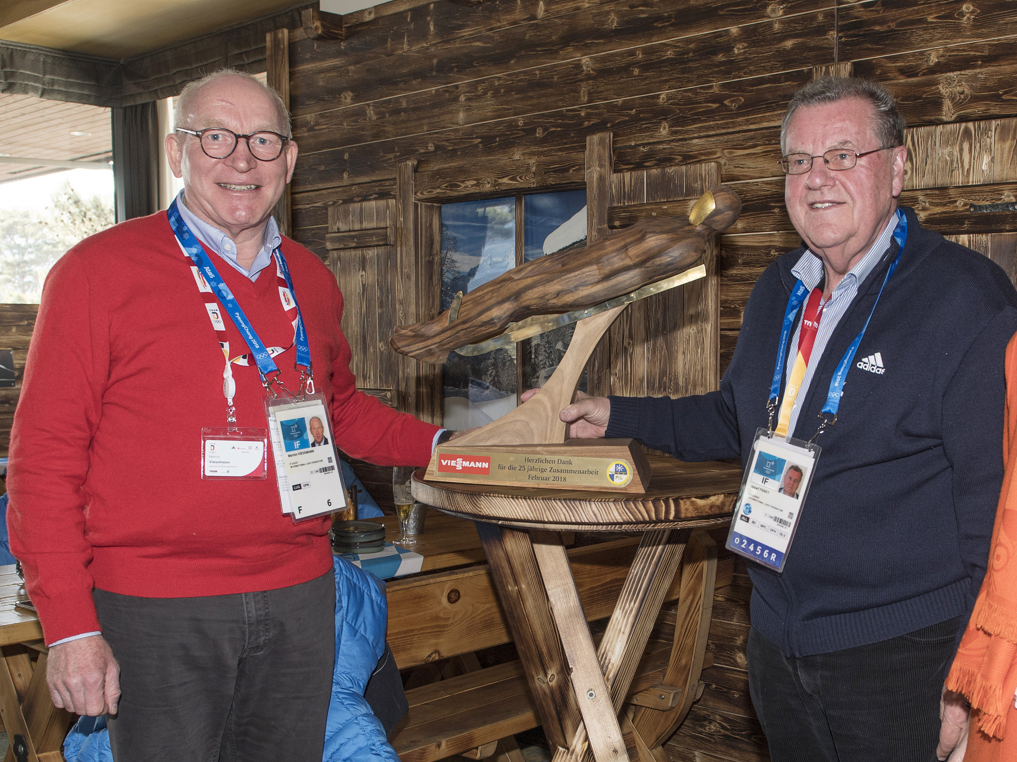 The hand-crafted sled was presented to Martin Viessmann, left, by FIL President Josef Fendt, right, during the Pyeongchang 2018 Winter Olympic Games ©FIL