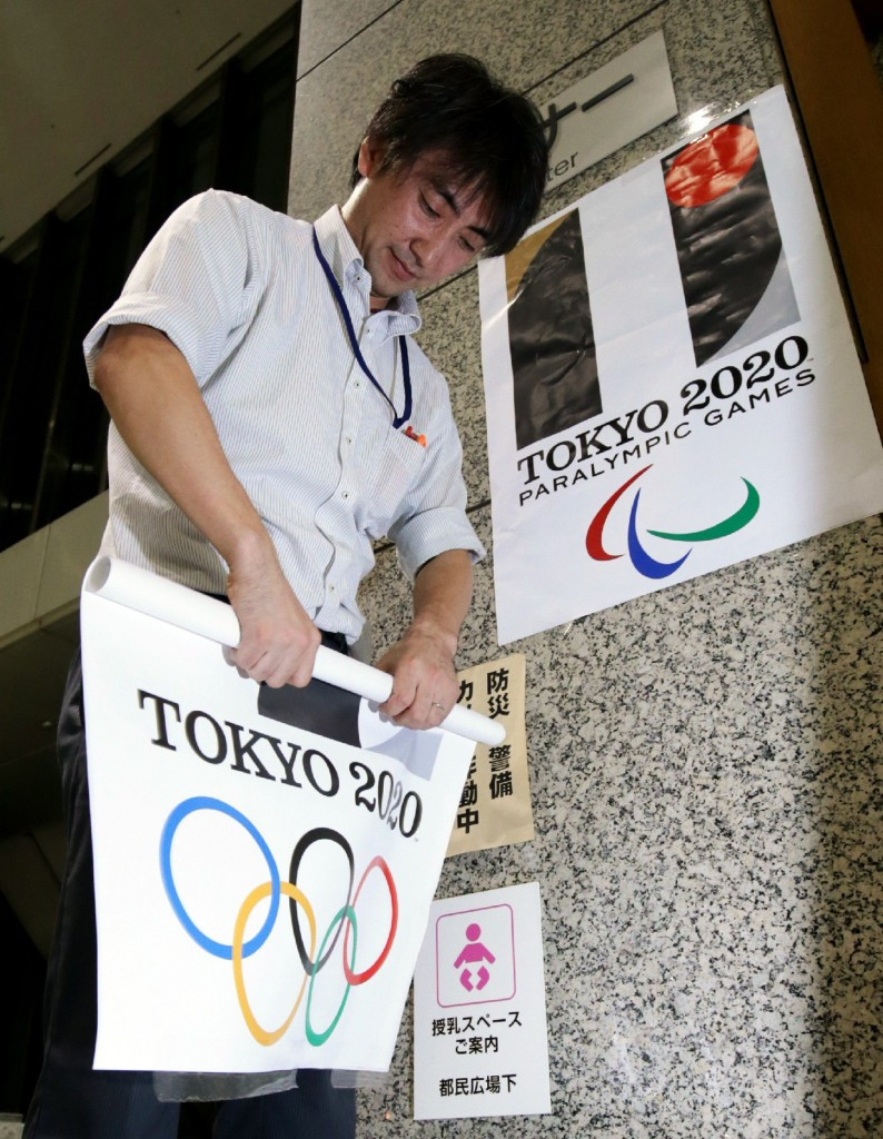 A Tokyo Metropolitan Government officer removes a poster showing the logo of the Tokyo 2020 Olympic Games